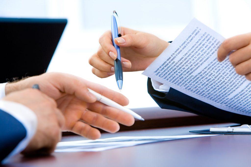 Smlouva o převodu nemovitosti – ověření podpisu na smlouvě, dva lidé podepisují dokumenty